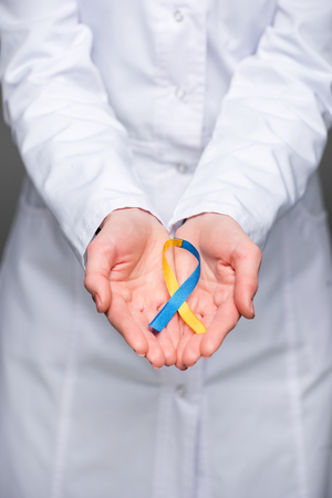 Foto de Female doctor hands holding Down Syndrome Day symbol blue and yellow ribbon - Imagen libre de derechos