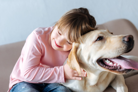 Foto de Happy child with down syndrome and Labrador retriever dog cuddling on sofa - Imagen libre de derechos