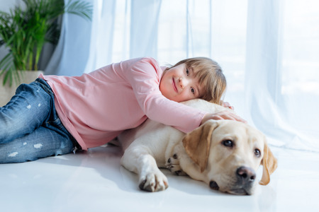 Foto de Happy kid  with down syndrome and Labrador retriever cuddling on the floor - Imagen libre de derechos
