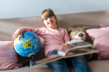 Foto de Child with down syndrome reading book and playing with globe - Imagen libre de derechos