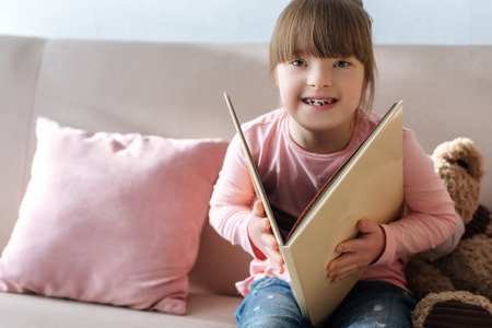 Foto de Laughing kid with down syndrome reading book - Imagen libre de derechos