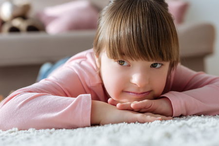 Foto de Dreamy child with down syndrome lying on floor in cozy room - Imagen libre de derechos
