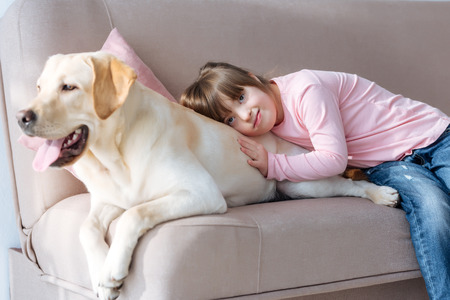 Foto de Kid with down syndrome lying on the sofa with Labrador retriever dog - Imagen libre de derechos