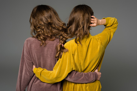 Photo pour back view of twins hugging with hair in one braid isolated on grey - image libre de droit