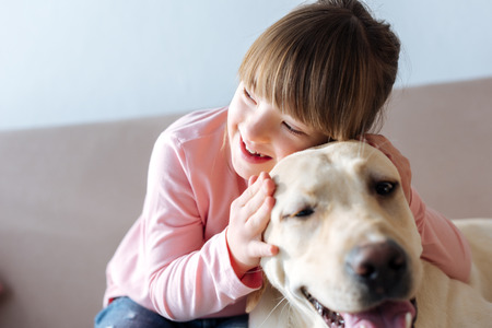 Foto de Kid with down syndrome hugging dog on sofa - Imagen libre de derechos
