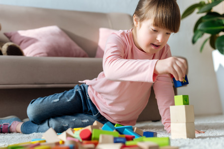 Foto de Child with down syndrome playing with toy cubes on floor in cozy room - Imagen libre de derechos