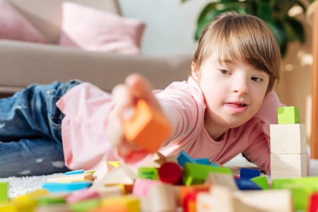 Foto de Kid with down syndrome building with toy cubes - Imagen libre de derechos