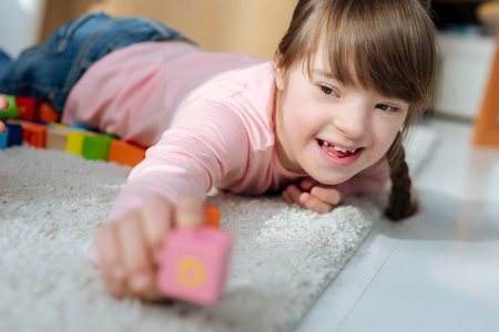 Foto de Child with down syndrome holding toy cube - Imagen libre de derechos