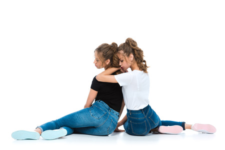 Photo pour back view of attractive young twins hugging and sitting on floor on white - image libre de droit