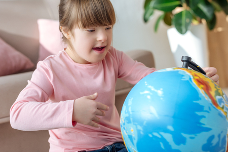 Foto de Child with down syndrome looking at globe - Imagen libre de derechos