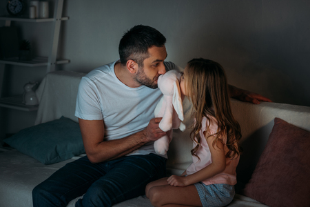 Photo pour father and little daughter kissing toy while sitting on sofa at home - image libre de droit