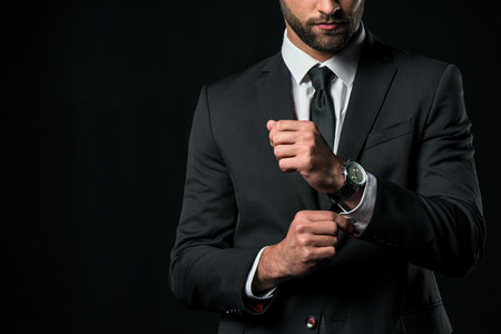 Foto de cropped view of businessman in jacket with wristwatch, isolated on black - Imagen libre de derechos