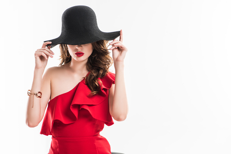 Photo pour attractive fashionable girl hiding eyes under black hat isolated on white - image libre de droit