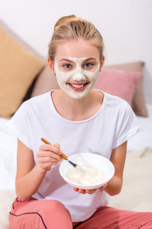 Photo pour young woman applying clay mask on face at home and looking at camera - image libre de droit