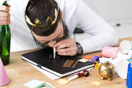 Foto de businessman with bottle of champagne taking drugs at workplace in office - Imagen libre de derechos