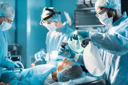 Foto de african american anesthetist holding oxygen mask above patient - Imagen libre de derechos