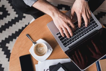 Photo pour cropped shot fo man using laptop on coffee table - image libre de droit
