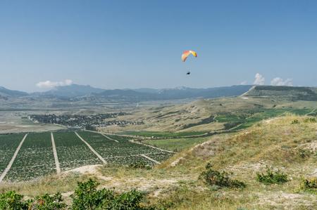 Foto de Parachutist gliding in blue sky over scenic landscape of Crimea, Ukraine, May 2013 - Imagen libre de derechos