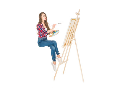 Foto de young woman levitating and painting on easel isolated on white - Imagen libre de derechos