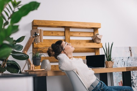 Photo for side view of girl stretching on chair in office - Royalty Free Image