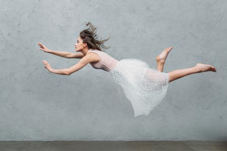 Foto de beautiful young woman in dress levitating and looking away on grey - Imagen libre de derechos