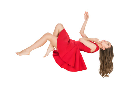 Foto de young woman in red dress falling with closed eyes isolated on white - Imagen libre de derechos