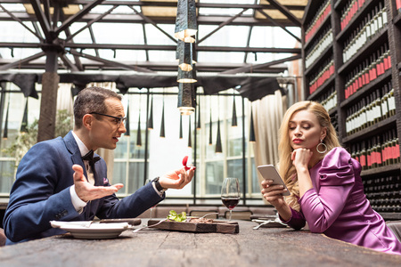 Photo pour man proposing his girlfriend while she using smartphone with bored expression at restaurant - image libre de droit