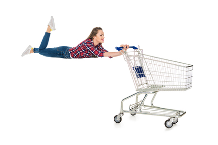 Foto de happy young woman levitating with empty shopping trolley isolated on white - Imagen libre de derechos