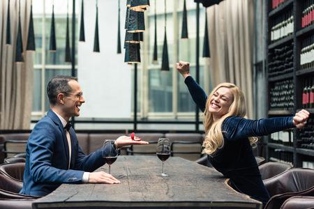 Photo pour side view of handsome adult man proposing his girlfriend at restaurant - image libre de droit