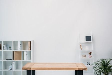 Photo for modern office interior with empty wooden table and folders on shelves - Royalty Free Image