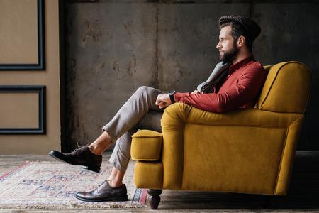 Photo pour fashionable bearded man sitting on yellow sofa - image libre de droit