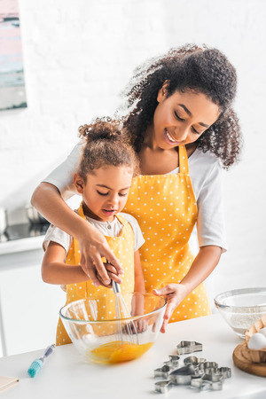 Foto de african american mother and daughter whisking eggs for dough together in kitchen - Imagen libre de derechos
