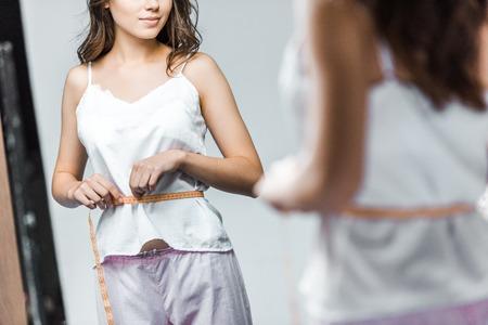 Foto de cropped view of woman measuring her waistline and looking at mirror - Imagen libre de derechos