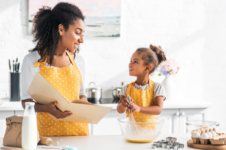 Photo pour african american mother holding cookbook and daughter preparing dough in kitchen, looking at each other - image libre de droit