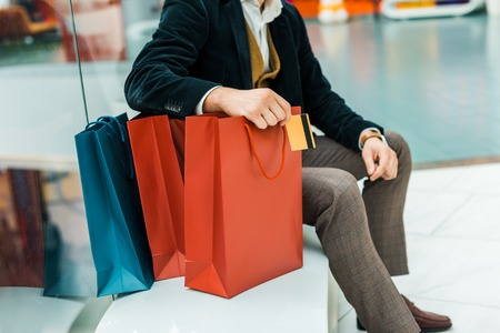 Foto de Cropped view of man holding credit card and sitting with bags in shopping mall - Imagen libre de derechos