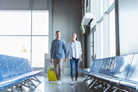 Foto de Romantic couple holding hands walking with yellow baggage in the airport - Imagen libre de derechos