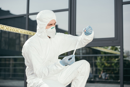 Photo pour Male criminologist in protective suit and latex gloves looking at evidence at crime scene - image libre de droit