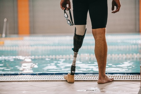 Foto de Cropped shot of swimmer with artificial leg standing in front of indoor swimming pool and holding swimming goggles - Imagen libre de derechos