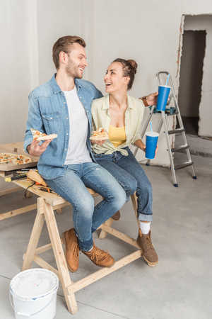 Photo pour Happy young couple with pizza and paper cups sitting together and smiling each other during repairment - image libre de droit