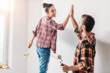 Photo pour Happy young couple giving high five while painting wall in new apartment - image libre de droit
