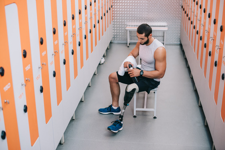 Foto de A handsome young sportsman with artificial leg sitting on bench at gym changing room - Imagen libre de derechos