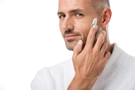 Photo pour Adult handsome man in bathrobe applying beauty cream on face isolated on white - image libre de droit
