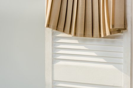 Photo for Close up of beige pleated skirt hanging on white room divider isolated on grey - Royalty Free Image