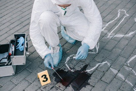 Photo pour Male criminologist in protective suit and latex gloves taking a blood sample at crime scene - image libre de droit