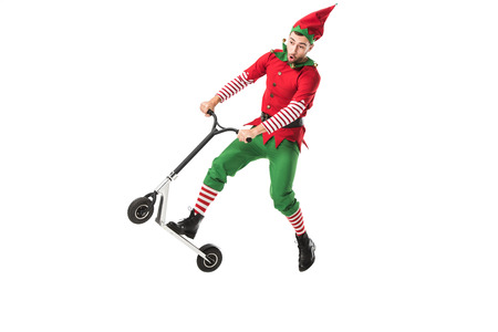 Photo for excited man in christmas elf costume jumping in air on push-cycle isolated on white - Royalty Free Image