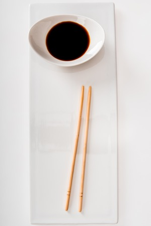 Photo pour Top view of plate with soy sauce and chopsticks on white slate isolated on white - image libre de droit