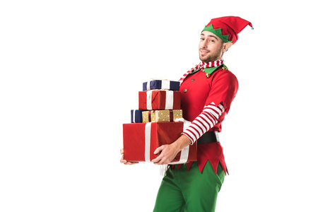 Photo for man in christmas elf costume looking at camera and carrying pile of presents isolated on white - Royalty Free Image