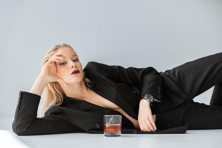 Foto de beautiful stylish half naked woman in black trendy suit lying on grey with glass of whiskey - Imagen libre de derechos