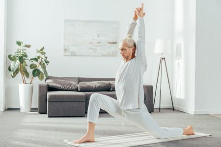 Foto de side view of man practicing Crescent Lunge on the Knee yoga pose at home - Imagen libre de derechos