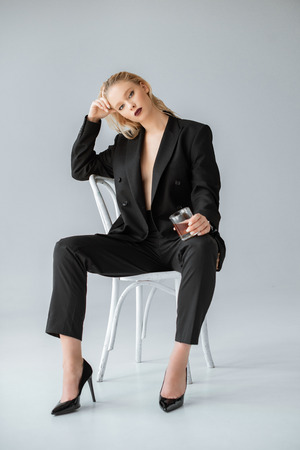 Photo pour fashionable woman in formal wear with glass of whiskey sitting on chair on grey - image libre de droit